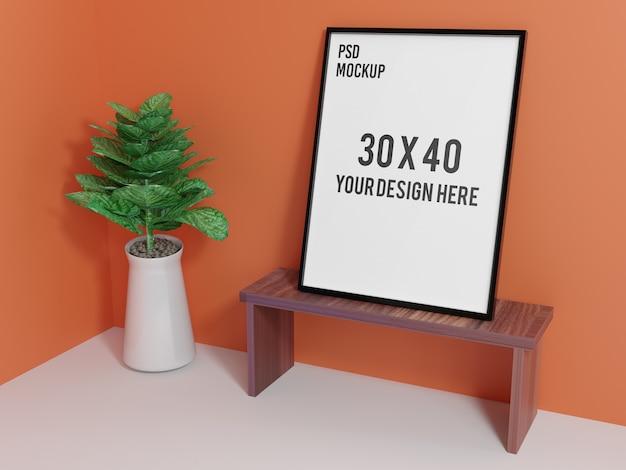 植物のたらいが付いている机の上に垂直フレームのモックアップ