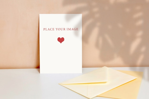 Vertical poster on a beige wall background, an envelope on the table, mockup, scene creator