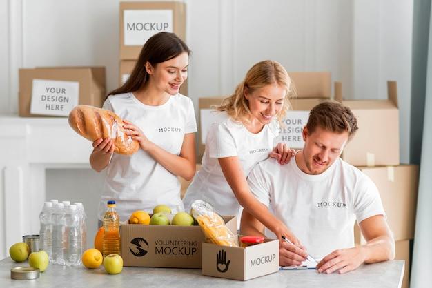 Волонтер записывает еду в коробки для пожертвований