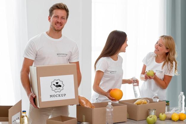 상자에 기부 할 음식을 준비하는 자원 봉사자