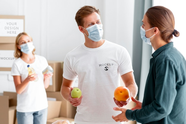 Volunteers with medical masks handing out food to man