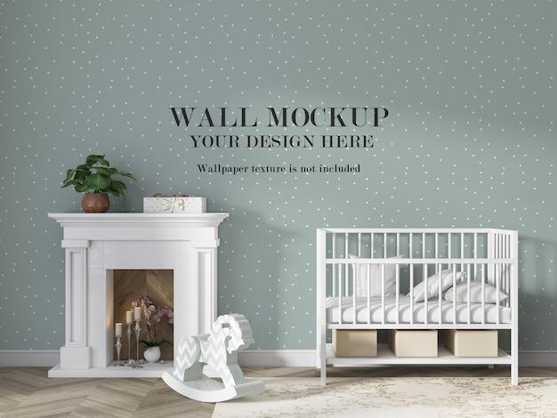 ミニマリストの家具が付いている白い赤ん坊のベッドの後ろの壁のモックアップ