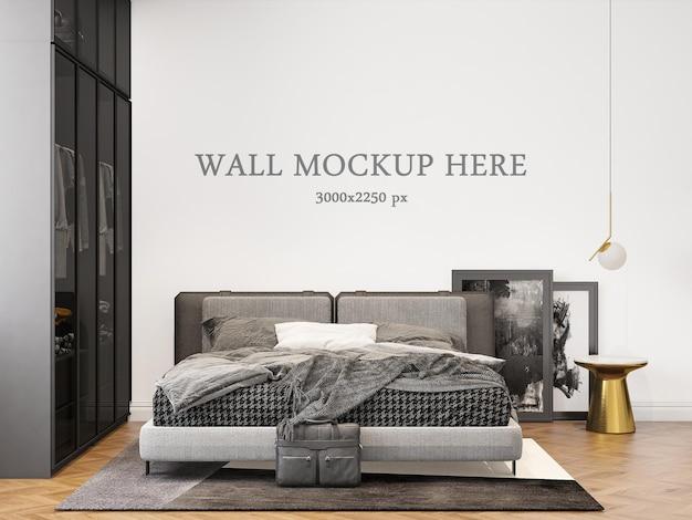 Wall mockup behind a dark bed in a modern bedroom