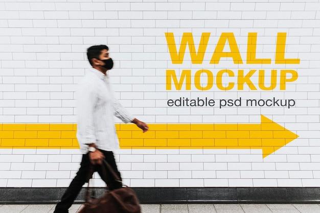 新しい通常の状態で通り過ぎて歩いている男性との壁のモックアップpsd