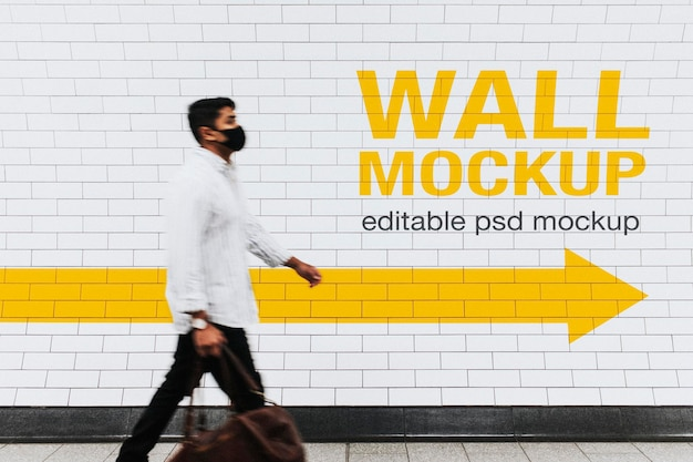 Wall mockup psd with a man walking past in the new normal