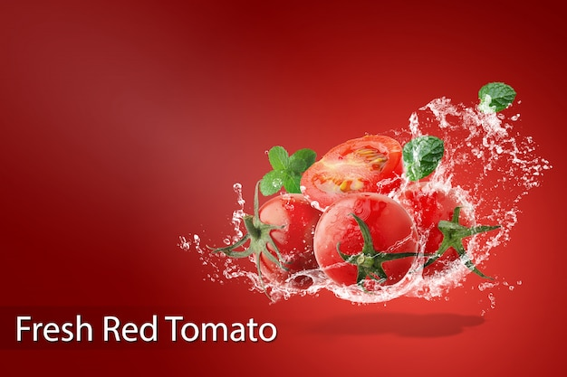 Water splashing on fresh red tomatoes over red background