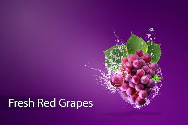 Вода брызгая на свежем красном винограде над красной предпосылкой.
