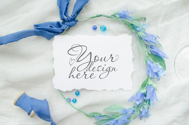 Wedding flat lay mockup with paper card and blue ribbon and wreath