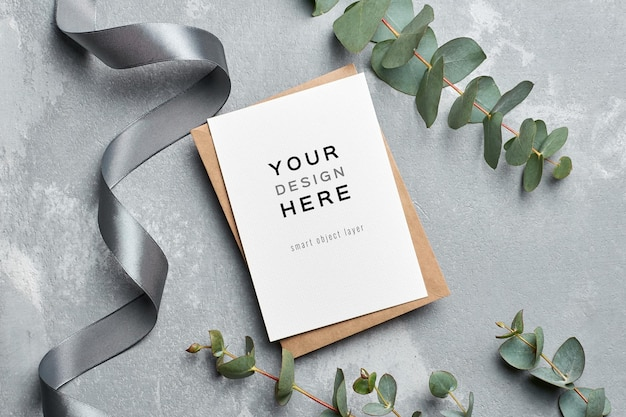 Wedding greeting card mockup with envelope and eucalyptus twigs on grey