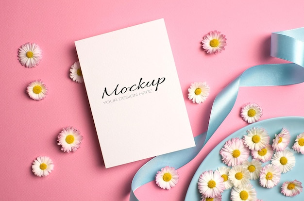 Wedding invitation card mockup with daisy flowers and ribbon on pink