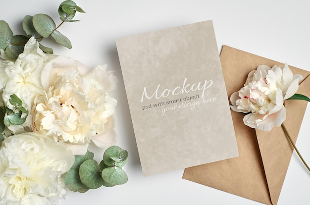 Wedding invitation or greeting card mockup with envelope and white peony flowers