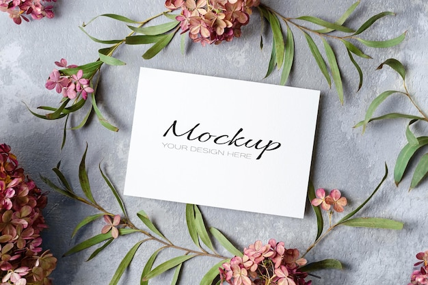 Wedding invitation or greeting card mockup with eucalyptus and hydrangea flowers
