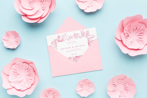 Wedding invitation mock-up with paper flowers on blue background
