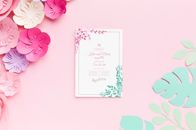 Wedding invitation mock-up with paper flowers on pink background