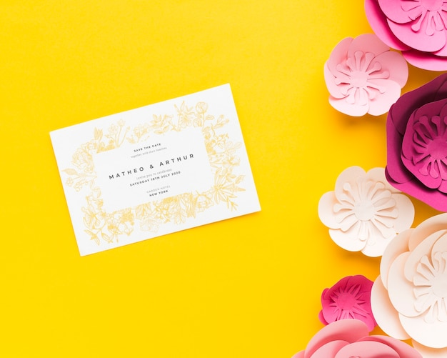 Wedding invitation mock-up with paper flowers on yellow wallpaper