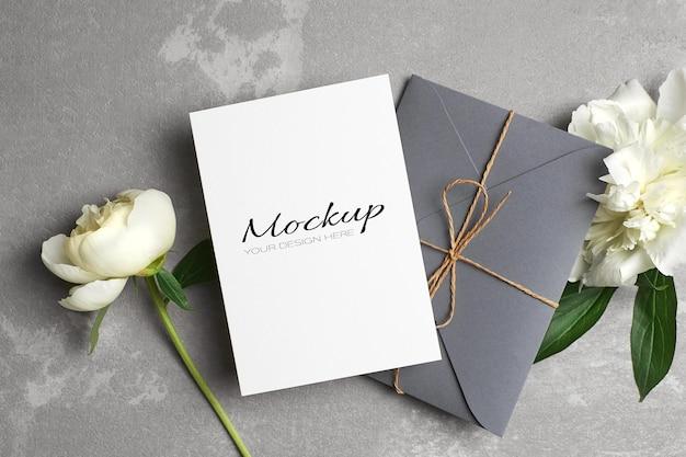 Свадебное приглашение или макет поздравительной открытки с конвертом и белыми цветами пиона на сером