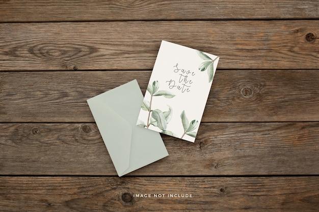 茶色の木製の背景に美しい葉を持つ結婚式の招待状のテンプレート