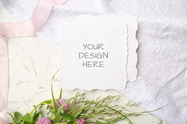Wedding mockup card with pink flowers and delicate silk ribbons on a white space