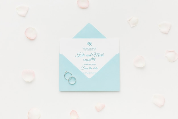 Wedding rings and invitation mock-up with petals