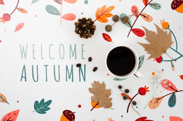 Welcome autumn lettering next to cup of coffee