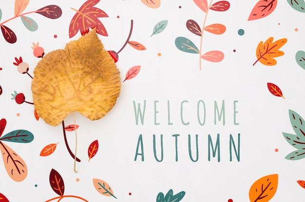 周りの葉で秋のレタリングを歓迎します。