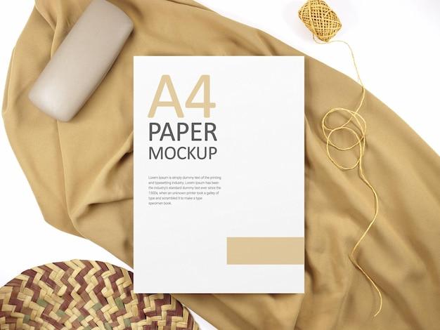 Белый бумажный макет формата а4 на коричневой ткани