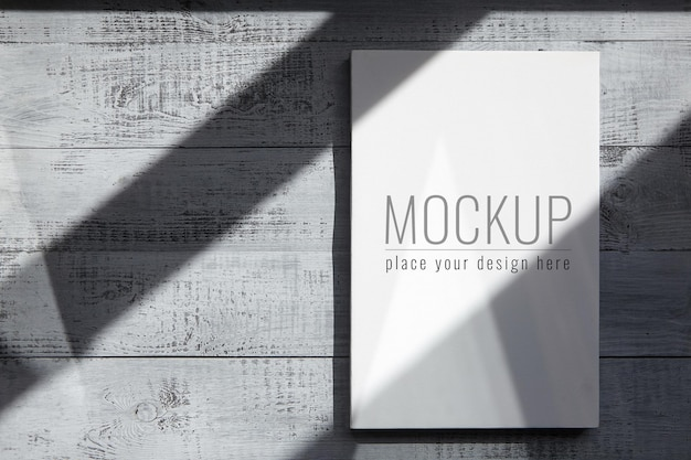 White blank canvas mockup hanging on grey wooden wall with shadows