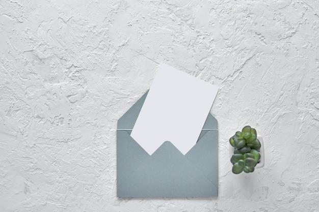 시멘트 배경에 봉투에 흰색 빈 카드입니다. 모형.