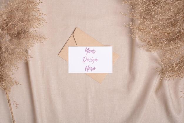 Белая пустая бумажная открытка и макет конверта с сухой травой пампасов на бежевой ткани нейтрального цвета