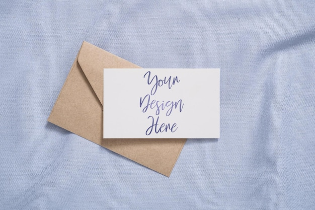 White blank paper card and envelope mockup on blue colored textile