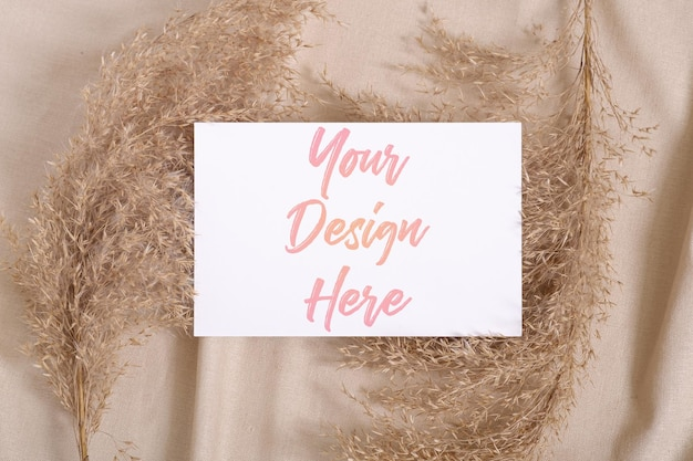 베이지 색 중립 색깔의 섬유에 팜파스 마른 잔디와 흰색 빈 종이 카드 모형