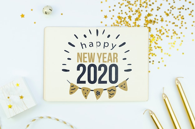 White card with happy new year 2020 quote and golden accessories