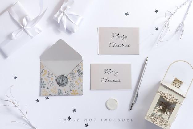 モックアップの手紙、ペン、ランタンとホワイトクリスマスの背景。