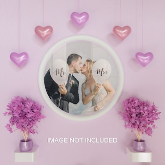 White circle frame photo mockup on pink wall with heart shaped hanging decoration