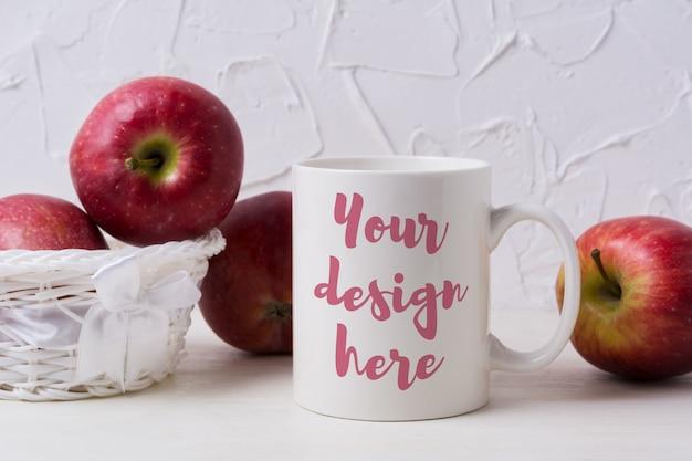 Макет кружка белого кофе с красными яблоками в плетеной корзине