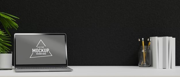 コピースペースが付いている白いコンピュータテーブル黒いセメントの壁が付いている空白のスクリーンのラップトップの付属品