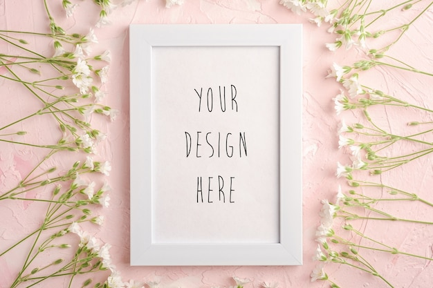 White empty photo frame mockup with mouse-ear chickweed flowers on pink textured background, top view copy space