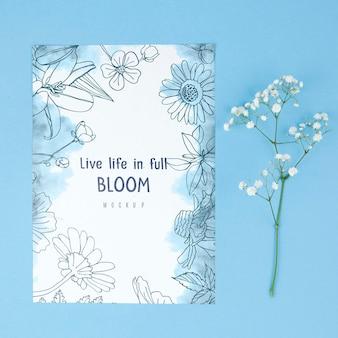 카드 모형 옆에 흰 꽃을 배치