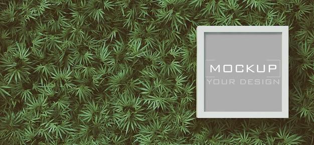 大麻の葉の背景に白いフレームのモックアップ