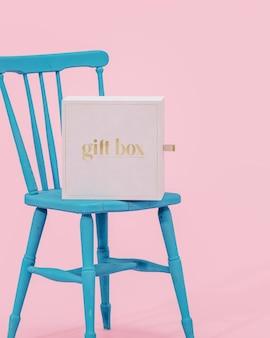 3dレンダリングをブランディングするための青い椅子ピンクの背景に白いギフトジュエリーボックスのモックアップ