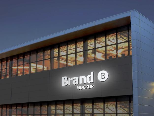 Белый световой 3d-макет логотипа на фасаде здания в ночное время