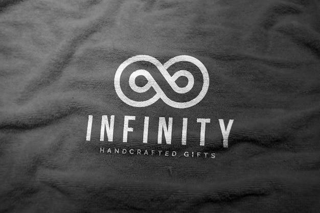 Белый логотип макет на черном тканевом полотенце