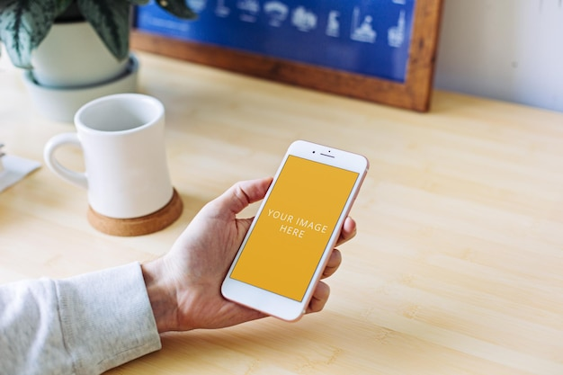 White phone screen mockup held in hand at home office