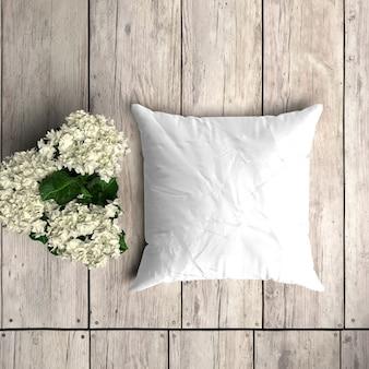 花飾り付きの木の板に白い枕カバーモックアップ