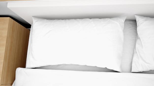 Белые подушки на кровати крупным планом
