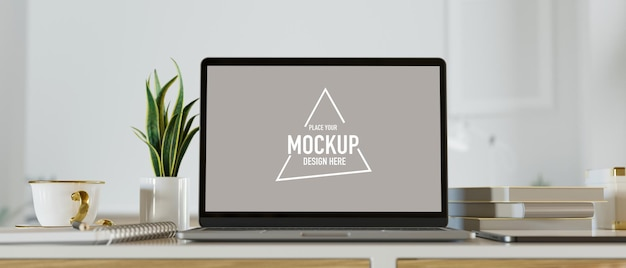 White screen laptop mockup with books small plant coffee mug on cozy work table white background