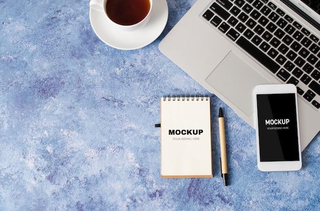 Белый смартфон с черным пустым экраном на офисном столе с ноутбуком, пустой блокнот и чашку чая