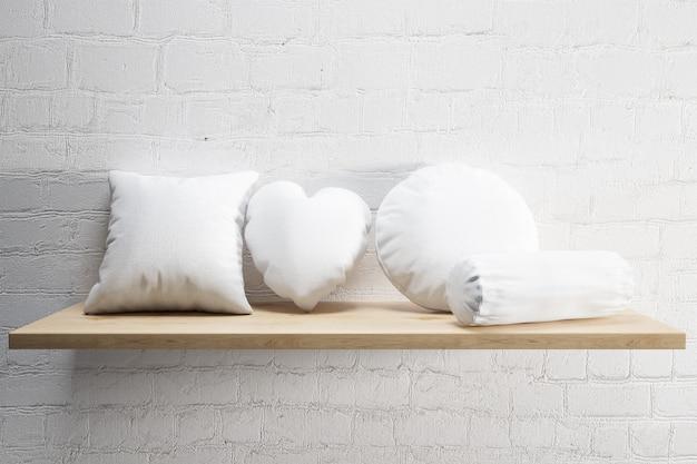Cuscini morbidi bianchi su una mensola in legno