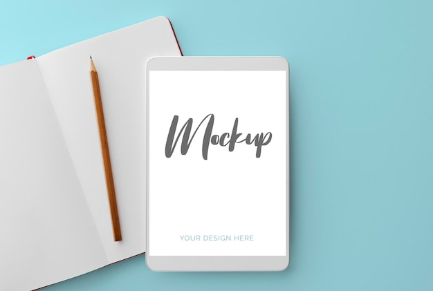 White tablet on blue with notebook and pencil mockup