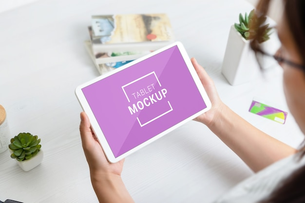 White tablet mockup in woman hands